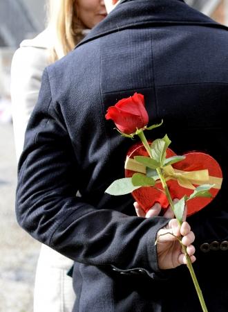 hombre romantico: Rom�nticos del hombre con la mujer hidding una rosa en su espalda como un regalo para el d�a de San Valent�n