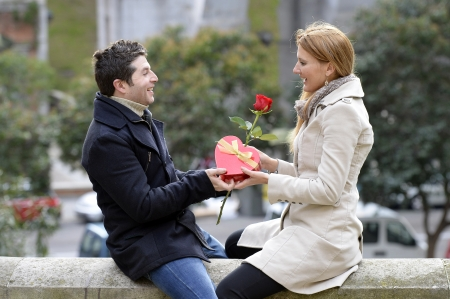 Romantic Man giving flower and heart shaped box to woman for valentines day photo