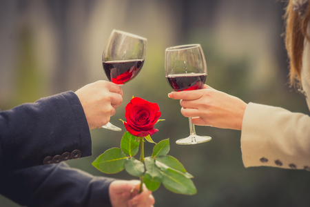 close up a romantic couple drinking wine with a rose in the mans hand on valentines day photo