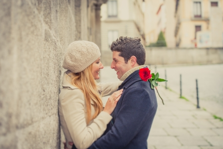 romantic kiss: young man giving his girlfriend a rose and kissing celebrating valentines day  Stock Photo
