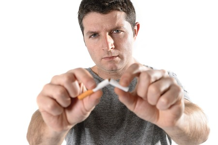 attractive man breaking cigarette with hands photo