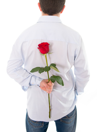 close up of a man wearing a blue shirt with a single red rose behind his back on a white background Stock Photo