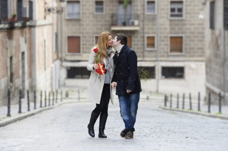 Romantic couple walking and kissing on Valentines day on urban background photo