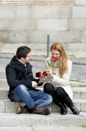 Romantic couple sitting on stairs on Valentines day with heart box and rose photo