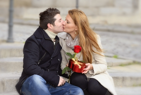 Romantic couple sitting on street kissing and holding a rose on valentines day photo