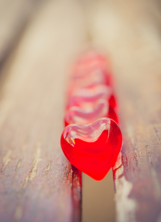heart break: close-up of ground of red love hearts sitting between two vintage planks of wood