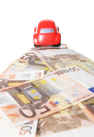 Back of a red toy car running on a road of euro bank notes on a white background   photo