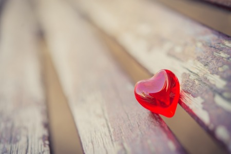 close-up of a red love heart sitting between two vintage planks of wood photo