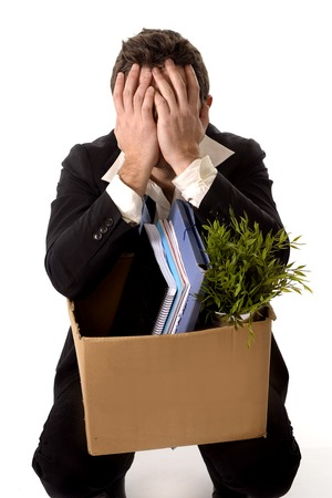 jobless: Jobless young Business Man with Cardboard Box Fired from Job isolated on White looking depressed, sad an in stress