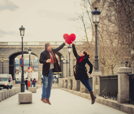 young attractive woman throwing a love heart shaped pillow to her boyfriend photo