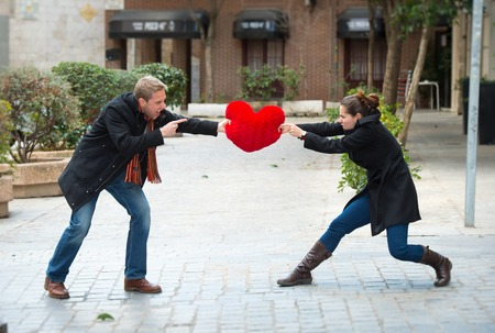 argument from love: young attractive couple fighting over a love hearted shaped pillow  Stock Photo