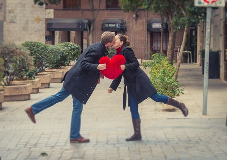 young attractive couple kissing with a big red love heart shaped pillow in the foreground  photo