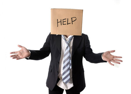 obscured face: Business man asking for help with cardboard box on his head isolated on white