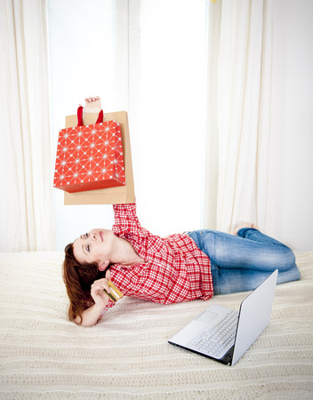 happy attractive red haired  woman wearing a red shirt  lying on her bed on her laptop online shopping on white background photo