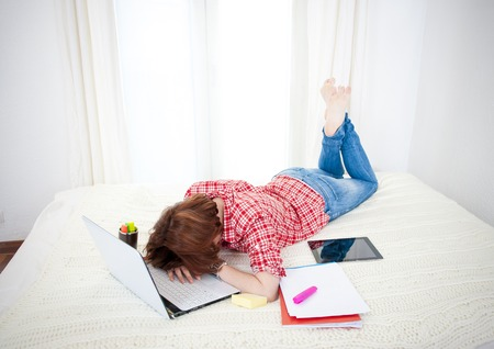 fatigued: red haired student, business woman lying  asleep on her laptop on a white