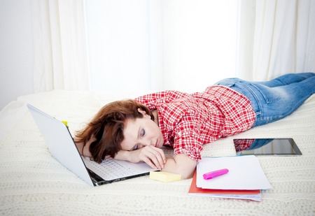 red haired student, business woman lying  asleep on her laptop on a white  photo