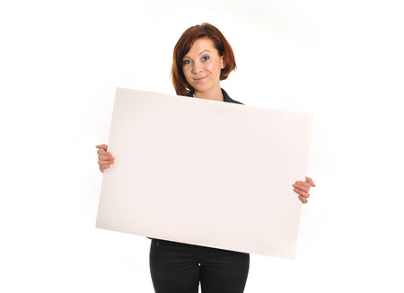 happy successful red hair business woman wearing a suit holding blank cardboard sign copy space on white  photo