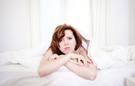 woman with red hair in her bed with insomnia and cant sleep on a white  photo