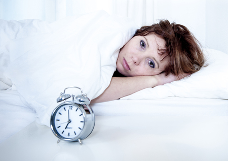 woman with red hair in her bed with insomnia and cant sleep waiting for her alarm clock to go off on a white