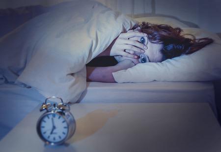 insomnio: Mujer con el pelo rojo en su cama con insomnio y no puede dormir a la espera de su reloj de alarma para que suene en un blanco