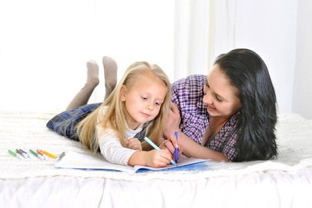 young Mother and little daughter on bed drawing together with markers isolated on white background photo