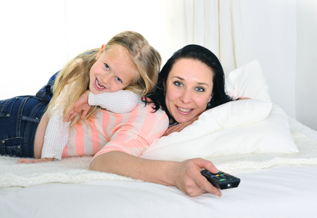 happy young mother holding remote and daughter watching television tv together photo