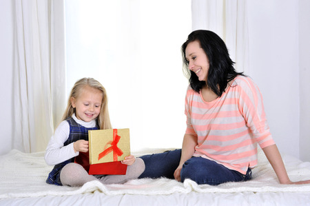Happy attractive young mother giving present to cute blonde daughter photo