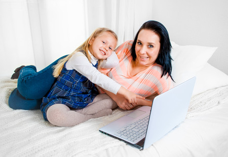 happy blonde haired daughter with her mum with brunette hair sitting on a bed sofa working on a laptop on a white background photo