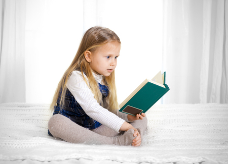 scared cute blonde haired school girl wearing a school uniform reading a book  on a white background  photo