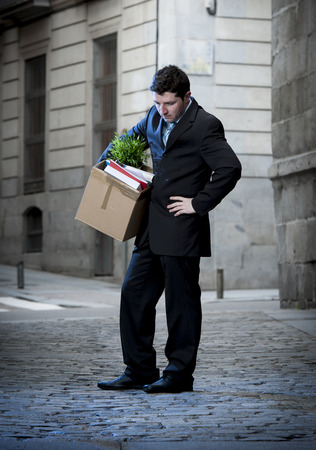 belongings:  frustrated business man fired in crisis carrying cardboard box on street