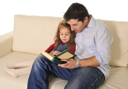 Father and sweet  little daughter reading book on couch together photo