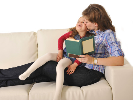 Mother and sweet  little daughter reading book on couch together photo