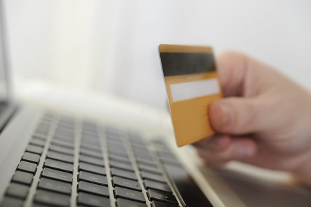 Man holding credit card in hand online shopping and banking with computer photo