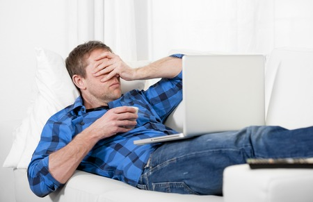 Young attractive man with headache and stress using Computer at home photo