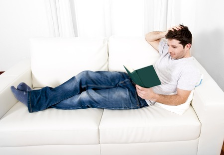 shocks: young attractive man reading book or studying on couch