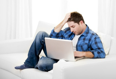 Young worried attractive man in stress using Computer at home photo