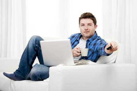 attractive relaxed man with Computer at home switching tv on photo