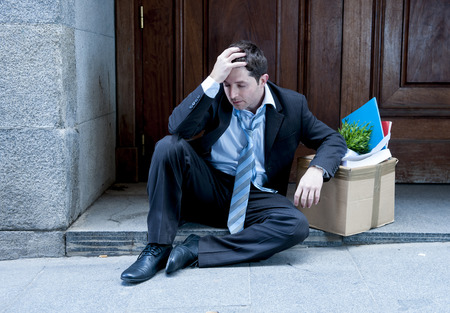desperate business man fired sitting on street with cardboard box