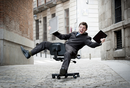 busy street: Happy crazy business man rolling downhill on chair with computer and tablet
