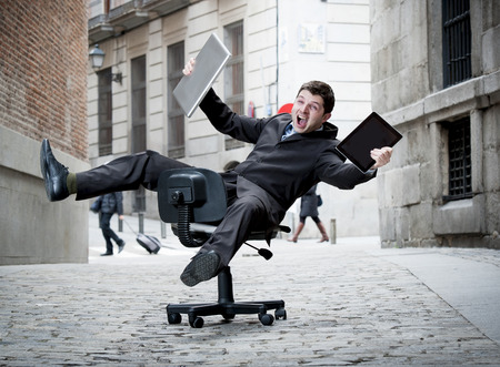 Happy crazy business man rolling downhill on chair with computer and tablet photo