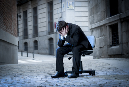 frustrated Business Man sitting on Office Chair on Street in stress and crying photo