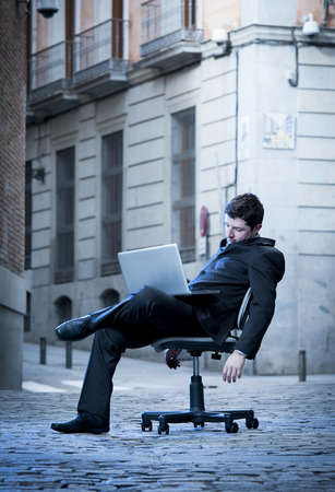 Exhausted Business Man sitting on Office Chair on Street sleeping photo