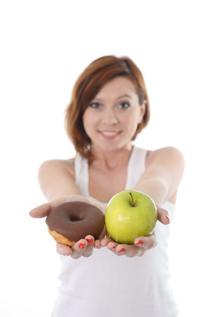Young sport Woman with Apple and Chocolate Donut in Hands to choose photo