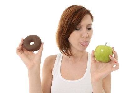 Young Attractive Woman holding Chocolate Donut sticks Tongue out to Apple photo
