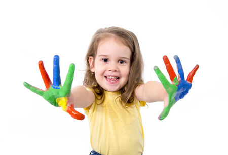 happy little girl with hands painted in vivid colours isolated on white background photo