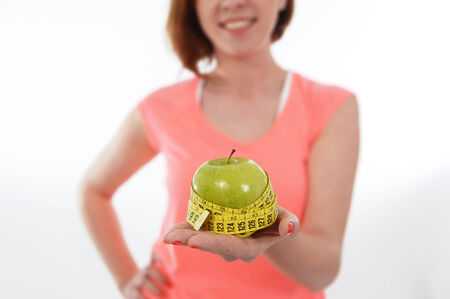 Happy young girl with apple and measure tape in diet sucess photo