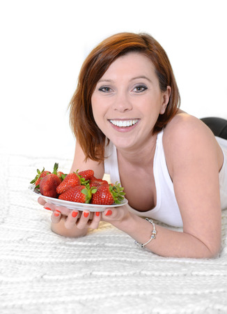 Attractive woman eating a bowl of strawberries in bed photo