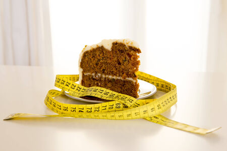 close up of carrot cake wrapped in a yellow measuring tape on a white table backlight with window in the background photo