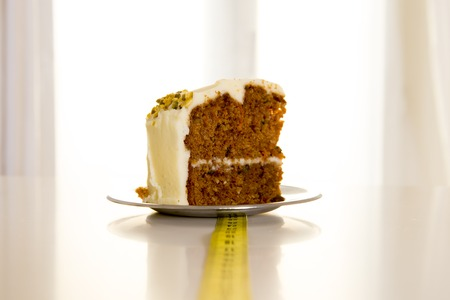carrot cake sitting on a measuring tape a concept to show when to diet  backlit with a white window in the background photo