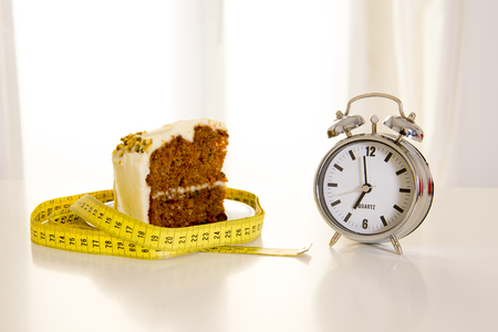 carrot cake wrapped in a measuring tape with a alarm clock, a concept to remind people when to start and not eat junk sugar foods backlit with a white window in the background photo